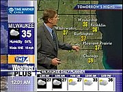 Local version of NBC Weather Plus from Milwaukee's WTMJ, showing an ad in the top-left corner, local branding above the WeatherPlus logo, and time in the bottom-left.