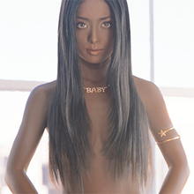 An image of recording artist Ayumi Hamasaki in front of a building window with a black wig covering her breasts. Her skin is digitally altered to make it look darker.
