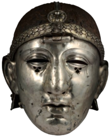 Colour photograph of the Emesa helmet, which has a silver face mask shaped like a human face, and an iron headpiece. The headpiece is decorated with a laurel-wreath diadem and a rosette, and has a central hinge holding the face mask.