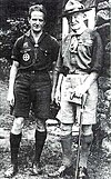 two men outdoors, both wearing Scout uniforms: short sleeve shirt, shorts and knee socks, the older man on the right wearing a campaign hat and holding a cane