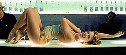 A woman with dark blonde hair is laying on a glass bar counter, which features a blue colour scheme. The woman is dressed in a pale green-tinged jersey top, gold lamé hotpants, and golden high-heels