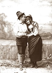 black and white photograph of young white woman in 16th-century peasant costume, embraced by young man also in period dress