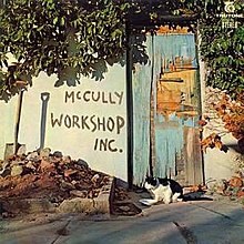 A colour photograph mid shot of a graffitied wall, a shovel leaning against it, and dilapidated blue door with a cat in front of it