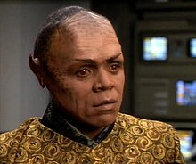 The dark-skinned Tom Wright is in makeup and costume as Tuvix. Black makeup is mottled across his cheeks and high brow, black straight hair is combed back from the hairline, pointed ear prosthetics have been applied, and amber-colored contact lenses are visible. The costume is colored in mustard and black like Tuvok's, but patterned in flowers and cut to a style like Neelix's customary clothing.