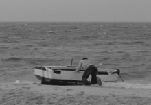 A black and white image showing a man as he pushes a rowboat over the sand and tries to get it into the choppy water. The boat, which is white on top and black on the bottom, is just entering the surf from the side.