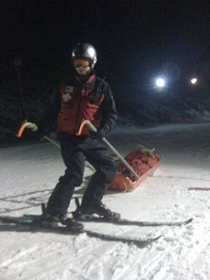 National Ski Patrol - A ski patroller with a rescue toboggan in tow