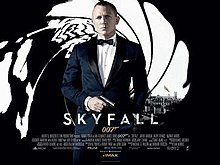 The poster shows a man wearing a tuxedo and holding a gun, standing in front of an image that looks like it was taken from the inside of a gun barrel, with the London skyline visible behind him. Text at the bottom of the poster reveals the film title and credits.