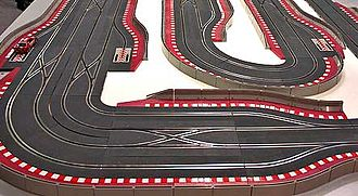 Slot car - Digital track (SCX, 1995). Digital technology allows cars to change lanes at crossing points and passing-lane sections.