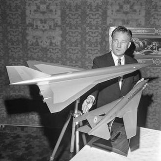 """Boeing 2707 - Federal Aviation Agency test pilot Joseph John """"Tym"""" Tymczyszyn displays models of SST designs from Lockheed, top, and Boeing, bottom. From Los Angeles Times, 14 July 1964."""