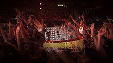 A close-up shot of fans inside a stadium during a concert, many of whom have their arms in the air. A transparent layer on top shows a concert stage with a curved video screen showing black-and-white images of musicians performing, with solid red and yellow colors below.