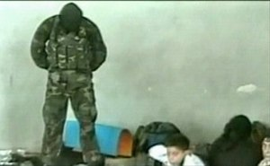 Beslan school siege - Masked hostage-taker standing on a dead man's switch during the second day of the crisis (a frame from the Aushev tape)