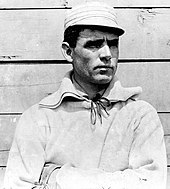 Clark Griffith standing against a wall and looking right, wearing a baseball uniform