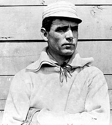 Medium black and white photo of white man with dark hair, mostly in profile, wearing an old fashioned baseball cap and uniform shirt