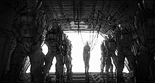 "Black-and-white drawing of a small woman, connected to wires, in front of wide open door, with two queues of large, suited soldiers in ""at attention"" pose flanking her either sides"