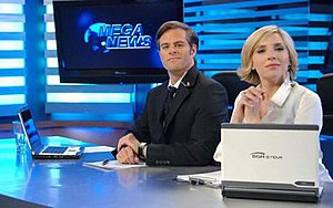 "Los exitosos Pells - Main characters Martín Pells (left, Mike Amigorena) and Sol Casenave (right, Carla Peterson), in the fictional news channel ""Mega News"" (whose logo can be seen in the background)"