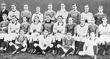 A black and white photograph of a football team in alternating light and dark shirts