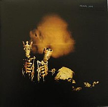 Two skeleton dolls wearing crowns stand on a darkened room with rocks. A single orange glows is seen behind them.