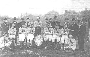 A faded photograph of a posed group of men, outdoors. At the front are six men sitting on benches and two seated on the ground, each dressed in sports clothing, a light-coloured shirt with darker trim, white shorts, dark socks and boots. Standing at the back are eight men, some bearded, wearing hats and coats, and three men in sports clothing. In front of the men is a large trophy in the form of a shield.