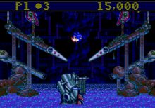 A screenshot of gameplay. The game's levels clearly represent a pinball machine with flippers to either side. Sonic the Hedgehog, who is acting as a pinball, is being propelled upwards in the centre of the screen after being hit by one of the flippers. The game's interface is shown at the top of the screen, showing the player's number of lives and total score.