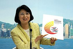 WTO 6th Ministerial Conference Co-ordination Office Head Janet Wong unveils the logo for the upcoming meeting. It incorporates the WTO's familiar six strokes, surrounding them with golden rays to form an image that looks like the number '6'