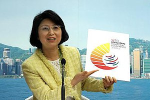 World Trade Organization Ministerial Conference of 2005 - WTO 6th Ministerial Conference Co-ordination Office Head Janet Wong unveils the logo for the upcoming meeting. It incorporates the WTO's familiar six strokes, surrounding them with golden rays to form an image that looks like the number '6'