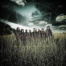 A group of nine men wearing masks stand in a field of grass with a gloomy clouded sky behind them.