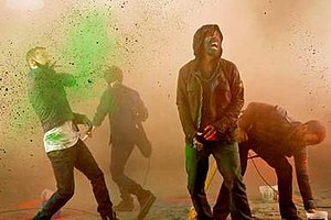 "The Catalyst - A behind-the-scenes screenshot of the music video, showing lead vocalists Chester Bennington and Mike Shinoda, lead guitarist Brad Delson and bassist Dave ""Phoenix"" Farrell throwing colored powder at each other."