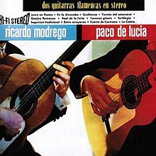 Two men playing flamenco guitars. It only shows their hands and the guitars.