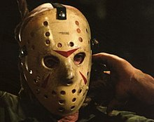 The actor wears a modified goalie mask. Three red triangles have been painted on the mask.