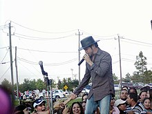 A man with a hat on his head, semi-inclined, wearing a colorful shirt and denim pants, holding a microphone in his left hand and holding the hand of a woman who hails from a crowd in the background. In the background you can see vehicles, poles and high voltage cables.