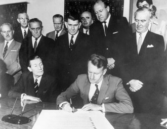 Zimbabwe - Ian Smith signing the Unilateral Declaration of Independence on 11 November 1965 with his cabinet in audience.
