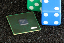 A photograph of the chip next to a pair of dice for size comparison
