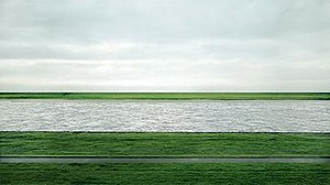 A grey river flowing horizontally through green fields under an overcast sky