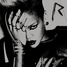 A black-and-white image of a woman wearing a leather jacket. Her hair is side-shaved, wears dark lipstick and her eye is covered with her hand. In the upper right corner there is an metal 'R' sign, while in the down right corner the words 'Rated R' are written in white letters.