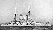 A large warship steaming through calm seas, thin puffs of smoke drift up from her three funnels