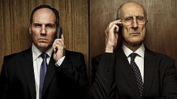 Head and shoulders of two serious-looking men in dark suits standing side-by-side, facing the camera, in front of dark wooden panels, each holding a phone to their ear.