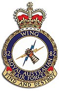 "Military crest of No. 82 Wing RAAF, topped with a crown and featuring a mailed fist holding two lightning bolts, beneath which appears the phrase ""Find and destroy"""