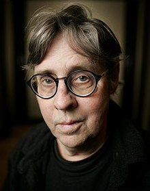 A portrait of Ryan Larkin, looking at the viewer, wearing a black shirt and circular-frame glasses. It is framed on a dark background.