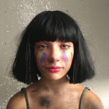 The artwork portrays the head and shoulders of a teenage girl wearing a black bobbed wig, with rainbow colours on her cheeks