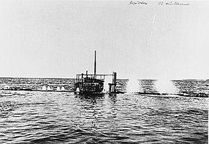 Фотография сделана около ватерлинии подводной лодки.  Почти весь корабль находится под водой, над поверхностью осталась только боевая рубка.  Можно увидеть струи воды, вырывающиеся из вентиляционных отверстий подводной лодки, когда она ныряет.