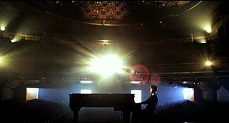U Smile - Bieber seen in an empty theater playing the piano while blue and yellow spot lighting is seen in the background.