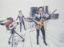 In a white studio, Geoff Downes is playing multiple keyboards and Trevor Horn playing a bass guitar, both wearing silver suits. A woman in a tube behind Horn is also wearing a silver costume.