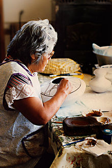 Helen Naha in her home decorating a pot in her Awatovi Star pattern
