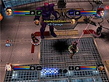 "In each corner of the screen a playable character's head appears, along with a red and blue bar extending horizontally back towards the center of the screen. At the bottom center five large circular ""X"" logos are seen, with three being brighter. To the left center are two glowing orbs with numbers representing their availability. In the center a beam is being fired at an off screen enemy, while another character advances towards a large robot."