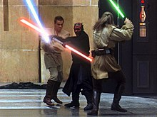 Three men fight with laser swords in an hangar.