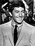 Photo of Dustin Hoffman, a young white man with dark hair, small eyes and a big nose, wearing a suit, in 1968.