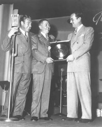 "Glenn Miller - First gold record award for ""Chattanooga Choo Choo"" is presented to Glenn Miller by W. Wallace Early of RCA Victor with announcer Paul Douglas on far left, February 10, 1942."