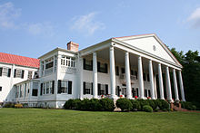 A two-story white house with red roof and columned porch.