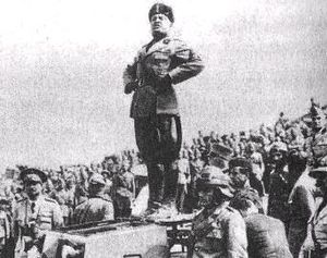 Caesarism - Italian Duce Benito Mussolini standing atop a tank and making a speech to soldiers of the Italian Army.