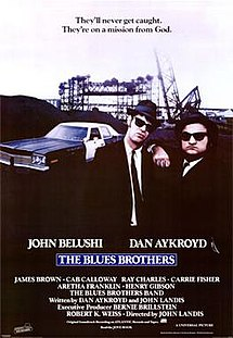"Movie poster with two of the main characters on the right-side of the image: They are both wearing black suits, hats, and sunglasses and facing forward. The man on the right is resting his arm on the shoulder of the man on the left. A police car is present on the left side of the image behind them. At the top of the image is the tagline, ""They'll never get caught. They're on a mission from God."" At the bottom of the poster is the title of the film, cast names, and production credits."